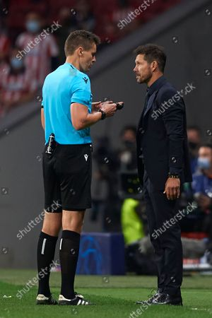 The referee Daniel Siebert and Diego Simeone head coach of Atletico Madrid talks during the UEFA Champions League group B match between Atletico Madrid and Liverpool FC at Wanda Metropolitano on October 19, 2021 in Madrid, Spain.