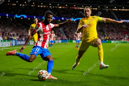 Atletico Madrid's Thomas Lemar, left, and Liverpool's Jordan Henderson duel for the ball during the Champions League Group B soccer match between Atletico Madrid and Liverpool at Wanda Metropolitano stadium in Madrid, Spain