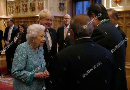 Britain's Queen Elizabeth II and Prime Minister Boris Johnson, left, greet guests at a reception for the Global Investment Summit in Windsor Castle, Windsor, England, Tuesday, Oct. 19, 2021.
