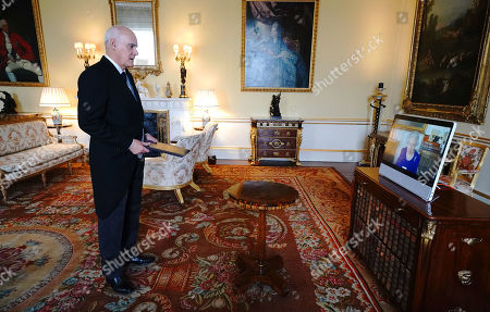 Queen Elizabeth II appears on a screen via videolink from Windsor Castle, where she is in residence, during a virtual audience to receive the Ambassador from the European Union, Joao de Almeida (left), at Buckingham Palace, London.