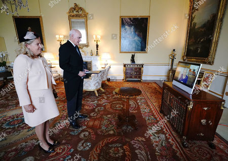 Queen Elizabeth II appears on a screen via videolink from Windsor Castle, where she is in residence, during a virtual audience to receive the Ambassador from the European Union, Joao de Almeida (centre), and Ana Jara de Carvalho (left), at Buckingham Palace, London.