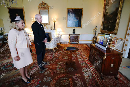 Stock Picture of Queen Elizabeth II appears on a screen via videolink from Windsor Castle, where she is in residence, during a virtual audience to receive the Ambassador from the European Union, Joao de Almeida (centre), and Ana Jara de Carvalho (left), at Buckingham Palace, London.