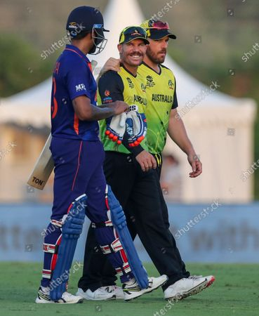 India's Suryakumar Yadav talks with Australia's David Warner and captain Aaron Finch, right, after defeating Australia by eight wickets in their Cricket Twenty20 World Cup warm-up match in Dubai, UAE