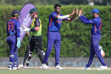 India's Ravichandran Ashwin, centre, is congratulated by a teammate after dismissing Australia's David Warner during the Cricket Twenty20 World Cup warm-up match between India and Australia in Dubai, UAE