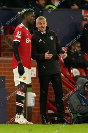 Manchester United's manager Ole Gunnar Solskjaer, right, talks to Manchester United's Paul Pogba during the Champions League Group F soccer match between Manchester United and Atalanta at Old Trafford, Manchester, England