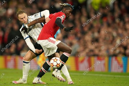 Atalanta's Teun Koopmeiners, left, challenges Manchester United's Paul Pogba during the Champions League Group F soccer match between Manchester United and Atalanta at Old Trafford, Manchester, England
