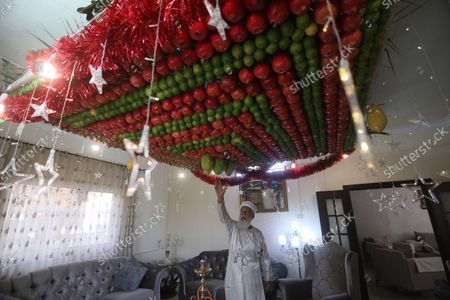 A member of the Samaritans religous group touches his ceiling decoration made of etrog and lulav fruits on the occasion of 'Sukkot', or 'Feast of Tabernacles' at their most sacred site at Mount Gerizim, in the northern West Bank City of Nablus, 21 October 2020. The festival begins on 21 October and lasts for one week. It is commemorating the ancient Israelites exodus from Egypt and their wandering in the desert for forty years before arriving in the holy land, according to the Torah.