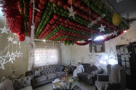 A member of the Samaritans religous group sits under his ceiling decoration made of etrog and lulav fruits on the occasion of 'Sukkot', or 'Feast of Tabernacles' at their most sacred site at Mount Gerizim, in the northern West Bank City of Nablus, 21 October 2020. The festival begins on 21 October and lasts for one week. It is commemorating the ancient Israelites exodus from Egypt and their wandering in the desert for forty years before arriving in the holy land, according to the Torah.