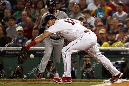 Boston Red Sox first baseman Kyle Schwarber makes an error as he can't handle a throw allowing Houston Astros' Michael Brantley to be safe at first during the sixth inning of Game 5 of the American League Championship Series, at Fenway Park in Boston