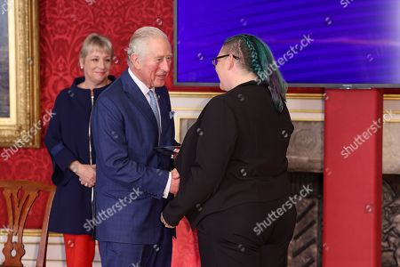 Prince Charles presents Kristin Topping with a Prince's Trust Award during the Prince's Trust Awards Trophy Ceremony at St James Palace on October 21, 2021 in London, England. The Prince's Trust Awards recognize young people who have succeeded against the odds, improved their chances in life and had a positive impact on their local community.