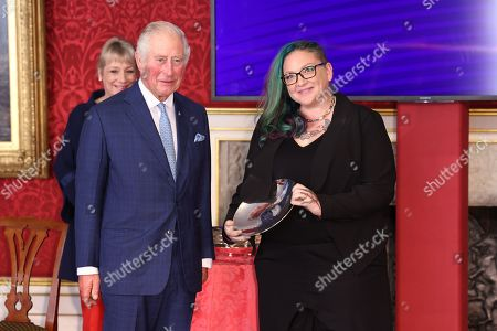 Stock Photo of Prince Charles presents Kristin Topping with a Prince's Trust Award during the Prince's Trust Awards Trophy Ceremony at St James Palace on October 21, 2021 in London, England. The Prince's Trust Awards recognize young people who have succeeded against the odds, improved their chances in life and had a positive impact on their local community.