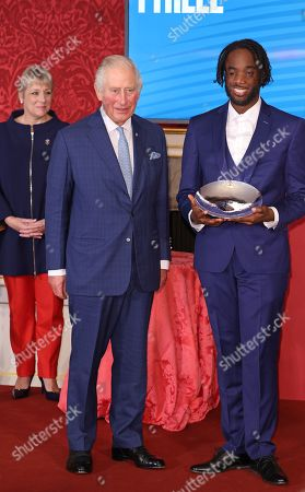 Stock Image of Prince Charles presents the Delta Air Lines Rising Star Award to Jhorvis Tyrell during the Prince's Trust Awards Trophy Ceremony at St James Palace on October 21, 2021 in London, England. The Prince's Trust Awards recognize young people who have succeeded against the odds, improved their chances in life and had a positive impact on their local community.