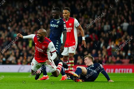Matt Targett of Aston Villa fouls Alexandre Lacazette of Arsenal for a penalty which was given after a VAR check by referee Craig Pawson