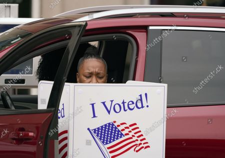 A voter makes their choice from a vehicle outside the American Airlines Center in Dallas. Republican Texas Gov. Greg Abbott, picked John Scott, an attorney who briefly joined former President Donald Trump's legal team last year as it challenged the 2020 election results, as the state's new elections chief