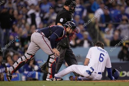 Stock Photo of Atlanta Braves catcher Travis d'Arnaud checks on Los Angeles Dodgers second baseman Trea Turner after he was hit with a pitch during the second inning in Game 5 of baseball's National League Championship Series, in Los Angeles