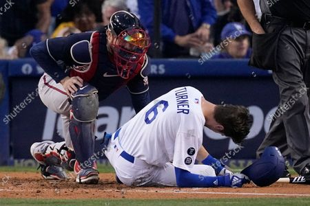 Atlanta Braves catcher Travis d'Arnaud checks on Los Angeles Dodgers second baseman Trea Turner after he was hit with a pitch during the second inning in Game 5 of baseball's National League Championship Series, in Los Angeles