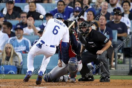 Los Angeles Dodgers' Trea Turner gets hit by a pitch as Atlanta Braves catcher Travis d'Arnaud stretches to handle the pitch during the second inning in game five in the 2021 National League Championship Series at Dodger Stadium on Thursday, Oct. 21, 2021 in Los Angeles, CA. (Luis Sinco / Los Angeles Times)