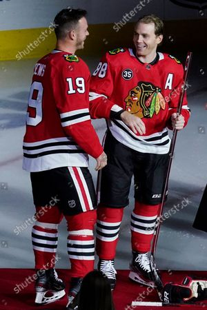 Stock Photo of Chicago Blackhawks right wing Patrick Kane, right, smiles as he is joined by center Jonathan Toews while being honored for his 1,000th career NHL hockey game, which happened in March, before the team's game against the Vancouver Canucks in Chicago