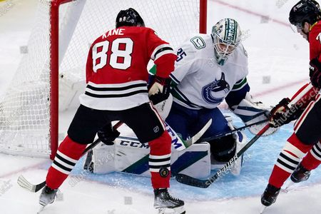 Vancouver Canucks goaltender Thatcher Demko (35) makes a save on a shot by Chicago Blackhawks right wing Patrick Kane, left, during the first period of an NHL hockey game in Chicago