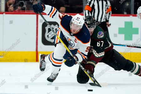 Stock Image of Edmonton Oilers center Connor McDavid (97) works against Arizona Coyotes left wing Lawson Crouse (67) for the puck during the second period of an NHL hockey game, in Glendale, Ariz