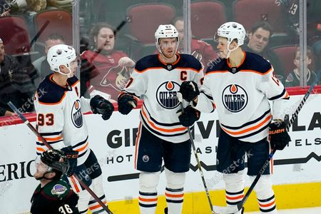 Edmonton Oilers center Connor McDavid, middle, celebrates his goal against the Arizona Coyotes with center Ryan Nugent-Hopkins (93) and right wing Jesse Puljujarvi (13) during the third period of an NHL hockey game, in Glendale, Ariz. The Oilers won 5-1