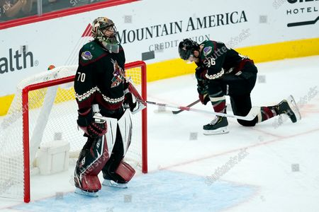 Stock Picture of Arizona Coyotes goaltender Karel Vejmelka (70) and right wing Christian Fischer (36) pause after a goal scored by Edmonton Oilers' Connor McDavid during the third period of an NHL hockey game, in Glendale, Ariz. The Oilers won 5-1