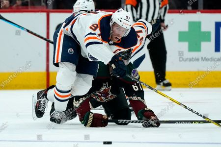 Edmonton Oilers center Connor McDavid (97) tangles with Arizona Coyotes left wing Lawson Crouse (67) during the second period of an NHL hockey game, in Glendale, Ariz