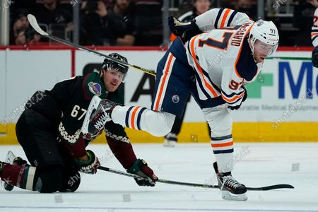Edmonton Oilers center Connor McDavid (97) moves to the puck after colliding with Arizona Coyotes left wing Lawson Crouse (67) during the second period of an NHL hockey game, in Glendale, Ariz