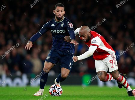 Arsenal's Alexandre Lacazette, right, duels for the ball with Aston Villa's Douglas Luiz during the English Premier League soccer match between Arsenal and Aston Villa at the Emirates stadium in London