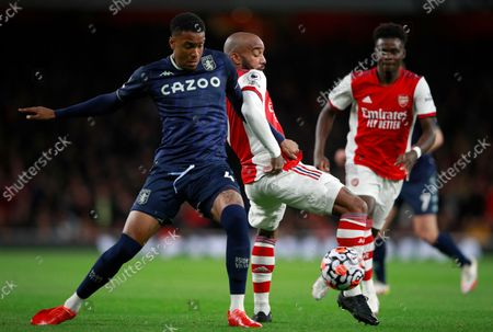 Aston Villa's Ezri Konsa, left, duels for the ball with Arsenal's Alexandre Lacazette during the English Premier League soccer match between Arsenal and Aston Villa at the Emirates stadium in London