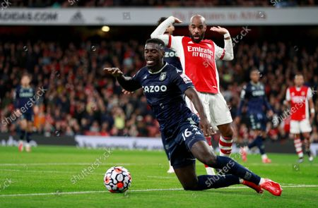 Aston Villa's Axel Tuanzebe, front, duels for the ball with Arsenal's Alexandre Lacazette during the English Premier League soccer match between Arsenal and Aston Villa at the Emirates stadium in London