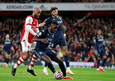 Aston Villa's Axel Tuanzebe, center, duels for the ball with Arsenal's Alexandre Lacazette during the English Premier League soccer match between Arsenal and Aston Villa at the Emirates stadium in London