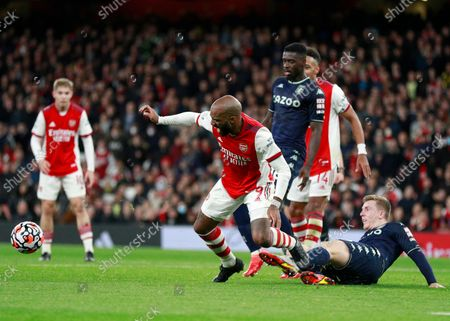 Arsenal's Alexandre Lacazette, center, duels for the ball with Aston Villa's Matt Targett, right, during the English Premier League soccer match between Arsenal and Aston Villa at the Emirates stadium in London
