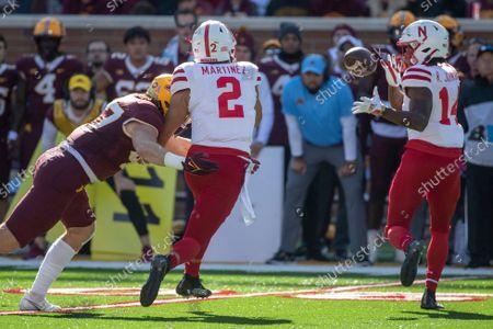 Nebraska quarterback Adrian Martinez (2) passes to running back Rahmir Johnson (14) as Minnesota linebacker Jack Gibbens (47) pressures the quarterback during an NCAA college football game, in Minneapolis. Minnesota won 30-23