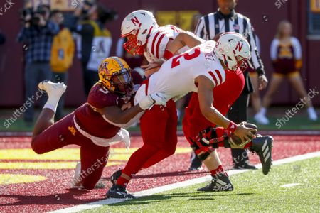 Minnesota defensive lineman Esezi Otomewo (9) drags Nebraska quarterback Adrian Martinez (2) into the end zone where he intentionally grounds the ball resulting in a safety as offensive lineman Bryce Benhart (54) tries to help in the fourth quarter of an NCAA college football game, in Minneapolis. Minnesota won 30-23