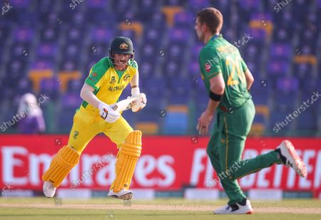 Australia's David Warner (L) runs between the wickets during the ICC Men's T20 World Cup cricket match between Australia and South Africa at Sheikh Zayed Cricket Stadium in Abu Dhabi, UAE, 23 October 2021.