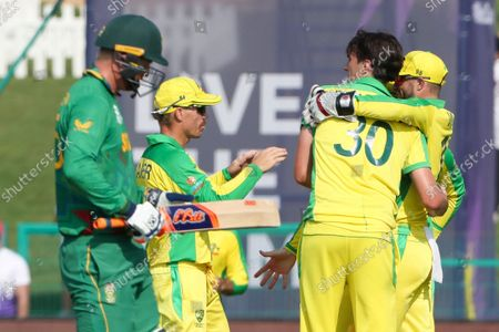 Stock Image of Australia's Pat Cummins is congratulated by teammate's Matthew Wade, right, and David Warner, second left, after taking the wicket of South Africa's Heinrich Klaasen, left, during the Cricket Twenty20 World Cup match between South Africa and Australia in Abu Dhabi, UAE