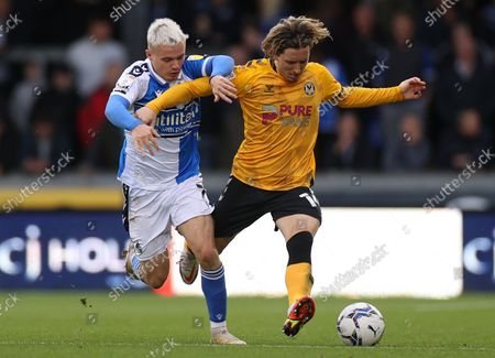 Aaron Lewis of Newport County is tackled by Luke Thomas of Bristol Rovers.