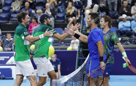 France's Nicolas Mahut, left, and Fabrice Martin are congratulated by Netherland's Wesley Koolhof, right, and Jean-Julien Rojer after winning the European Open tennis tournament in Antwerp, Belgium