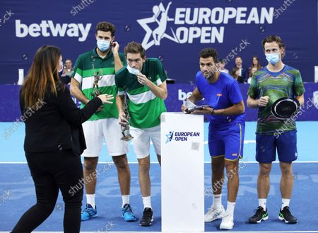 First place, France's Nicolas Mahut and Fabrice Martin, left, and Netherland's Wesley Koolhof and Jean-Julien Rojer, right, receive instruction from an organiser before posing with their trophies after the men's doubles final at the European Open tennis tournament in Antwerp, Belgium