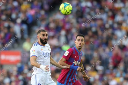 FC Barcelona's midfielder Sergio Busquets (R) duels for the ball with Real Madrid's striker Karim Benzema (L) during the Spanish LaLiga soccer match between FC Barcelona and Real Madrid at Camp Nou stadium in Barcelona, Catalonia, Spain, 24 October 2021.