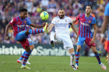 FC Barcelona's midfielder Sergio Busquets (R) and striker Ansu Fati (L) duel for the ball with Real Madrid's striker Karim Benzema (C) during the Spanish LaLiga soccer match between FC Barcelona and Real Madrid at Camp Nou stadium in Barcelona, Catalonia, Spain, 24 October 2021.