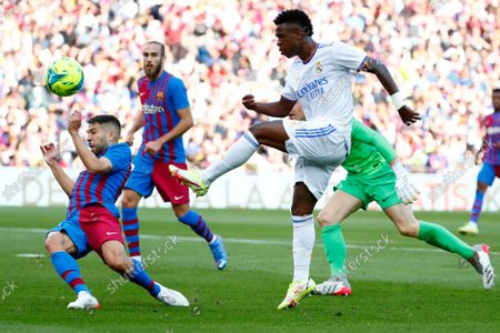 Barcelona's Jordi Alba, left, tries to block a shot by Real Madrid's Vinicius Junior during the Spanish La Liga soccer match between FC Barcelona and Real Madrid at the Camp Nou stadium in Barcelona, Spain