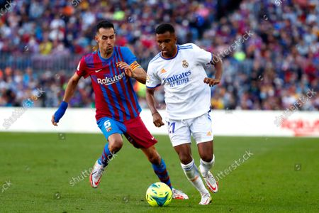 Barcelona's Sergio Busquets, left, challenges Real Madrid's Rodrygo during the Spanish La Liga soccer match between FC Barcelona and Real Madrid at the Camp Nou stadium in Barcelona, Spain
