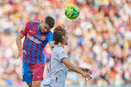 Jordi Alba of Barcelona and Luka Modric of Real Madrid compete for the ball during the La Liga Santander match between FC Barcelona and Real Madrid CF at Camp Nou on October 24, 2021 in Barcelona, Spain.