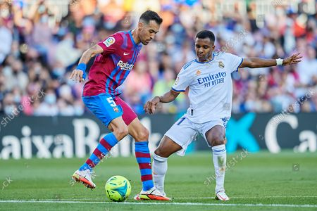 Sergio Busquets of Barcelona and Rodrygo of Real Madrid compete for the ball during the La Liga Santander match between FC Barcelona and Real Madrid CF at Camp Nou on October 24, 2021 in Barcelona, Spain.