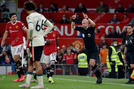 Stock Photo of Referee Anthony Taylor signals he has checked the VAR and is showing a red card to Manchester United's Paul Pogba during the English Premier League soccer match between Manchester United and Liverpool at Old Trafford in Manchester, England
