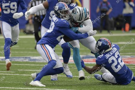 New York Giants' Xavier McKinney (29) and Adoree' Jackson (22) tackle Carolina Panthers' Royce Freeman (32) during the first half of an NFL football game, in East Rutherford, N.J