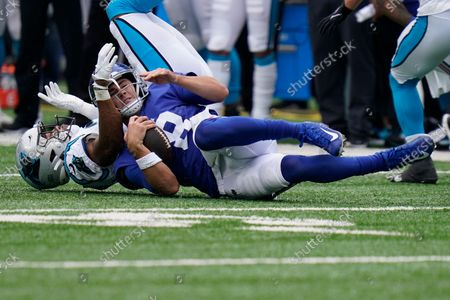 New York Giants quarterback Daniel Jones (8) is tackled during the first half of an NFL football game against the Carolina Panthers, in East Rutherford, N.J