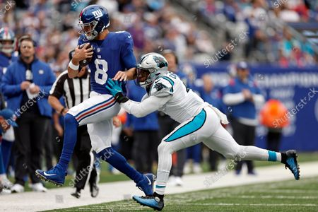 New York Giants quarterback Daniel Jones (8) is pushed out of bounds by Carolina Panthers linebacker Jermaine Carter (4) during an NFL football game, in East Rutherford, N.J